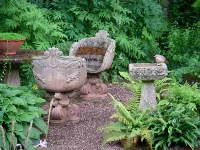 image: Quiet corner with ornate stone garden chairs and birdbath complete with thrush